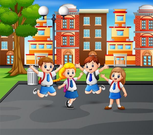 Crianças felizes de uniforme no salto no parque Vetor Premium