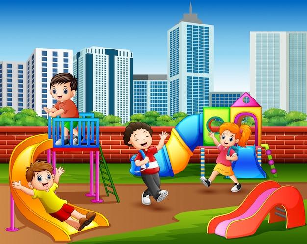 Crianças felizes do jardim de infância que jogam no campo de jogos Vetor Premium