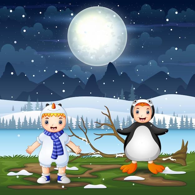 Crianças felizes em fantasias de animais na paisagem noturna de neve Vetor Premium