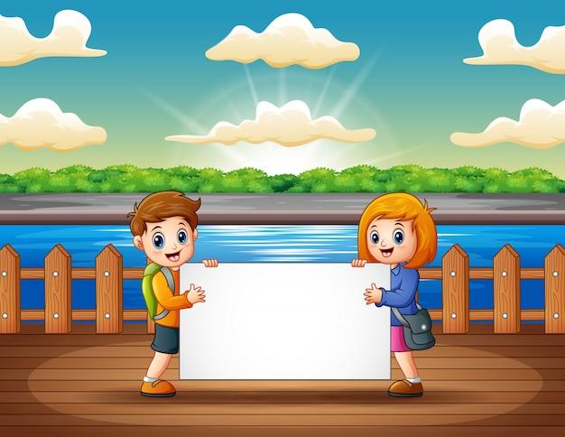 Crianças, segurando, sinal branco, em, a, madeira, cais Vetor Premium