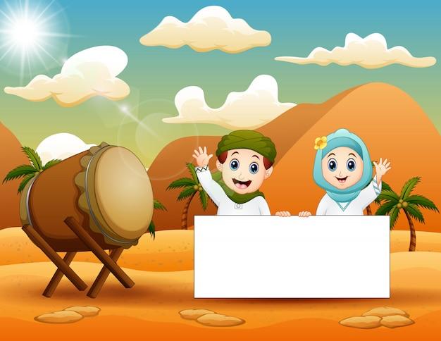 Cute, muçulmano, criança, segurando, em branco, sinal, em, a, deserto Vetor Premium