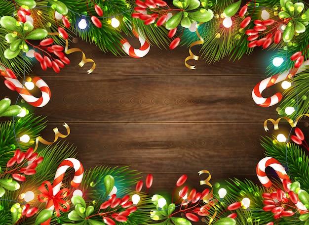 Decorações de natal brilhante com folhas de doces e luzes de fada no fundo de madeira marrom realista Vetor grátis