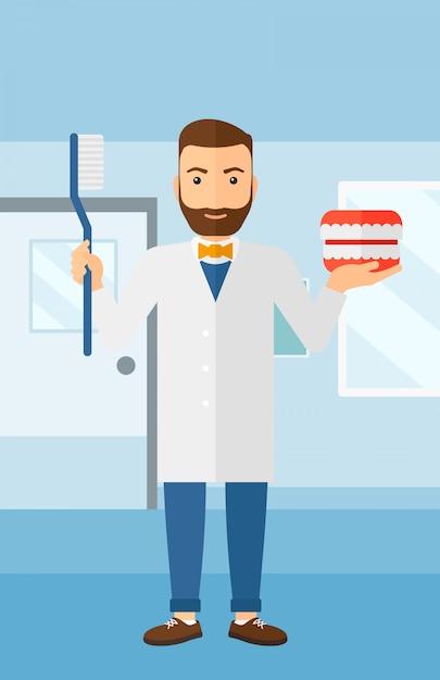 Dentista com modelo de maxila dental e escova de dentes. Vetor Premium