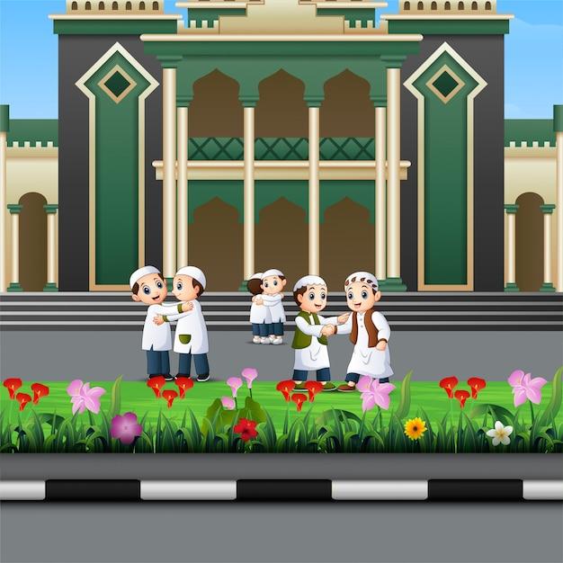 Desenho de crianças muçulmanas feliz na frente de uma mesquita Vetor Premium