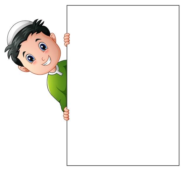 Desenho de menino muçulmano feliz segurando cartaz em branco Vetor Premium