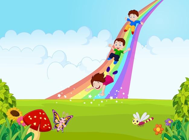 Desenhos animados criancinhas jogando slide arco-íris na selva Vetor Premium