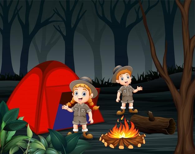 Desenhos animados de dois tratadores estão acampando em uma floresta escura Vetor Premium