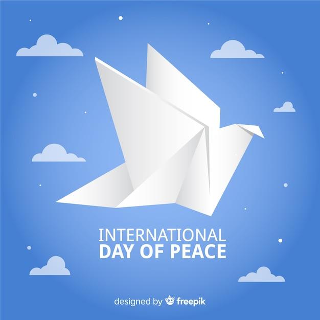Dia da paz de origami com pomba e nuvens Vetor grátis