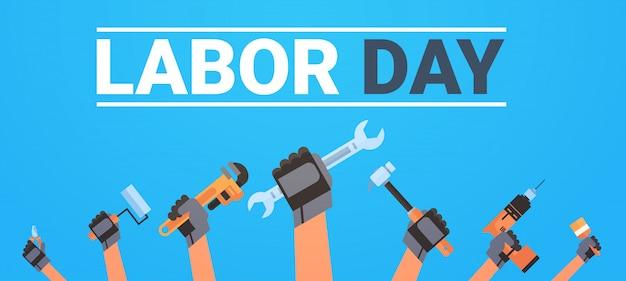 Dia do trabalho com as mãos segurando diferentes instrumentos de trabalho de férias Vetor Premium