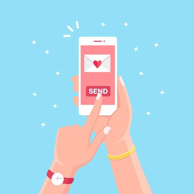 Dia dos namorados . envie ou receba amor sms, carta, e-mail com celular branco. mão humana segure o celular, smartphone em segundo plano. envelope com coração vermelho. Vetor Premium