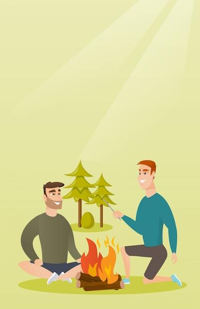Dois amigos sentados ao redor da fogueira no acampamento Vetor Premium