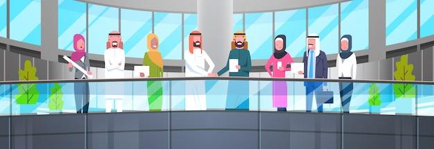 Dois, homem negócios árabe, líderes, aperto mão, sobre, equipe, de, muçulmano, pessoas negócio, em, modernos, escritório, parceria, e, acordo, conceito, horizontais, ilustração Vetor Premium