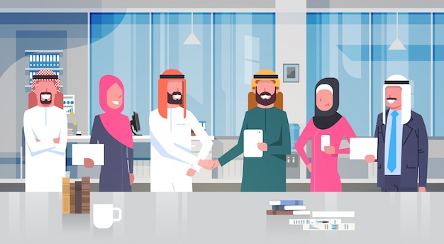 Dois, homem negócios árabe, líderes, aperto mão, sobre, equipe, de, muçulmano, pessoas negócio, em, modernos, escritório, parceria, e, acordo, conceito Vetor Premium