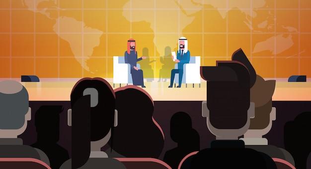 Dois homens de negócios árabes ou políticos em conferência ou debate reunião entrevista falando sobre mapa-múndi na frente da grande audiência Vetor Premium