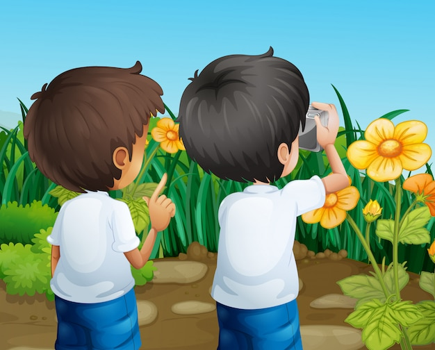 Dois meninos tirando fotos das flores Vetor grátis
