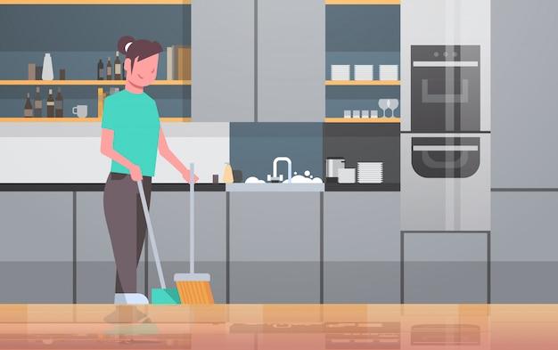 Dona de casa varrendo o chão com vassoura e colher jovem garota fazendo trabalhos domésticos conceito de faxina moderna cozinha interior feminino personagem de desenho animado Vetor Premium