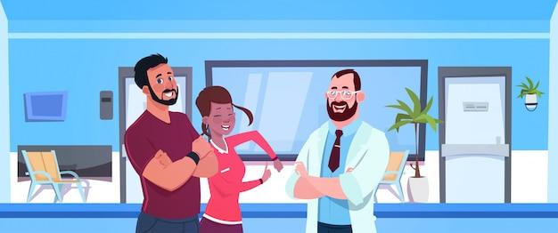 Doutor, falando, com, feliz, par doentes, sobre, hospitalar, sala de espera Vetor Premium