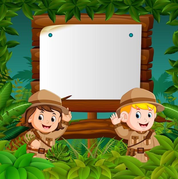 Duas crianças em uma aventura na selva com fundo de madeira em branco Vetor Premium