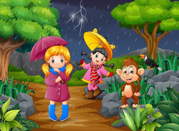 Duas menina carregando guarda-chuva vai sob uma chuva com macaco Vetor Premium