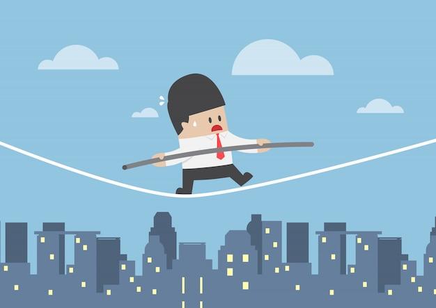 Empresário andando em uma corda sobre a cidade Vetor Premium