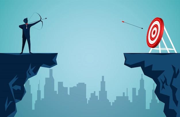 Empresário de pé no penhasco está atirando uma flecha do outro lado do penhasco em frente à seta para o alvo no centro do círculo vermelho Vetor Premium