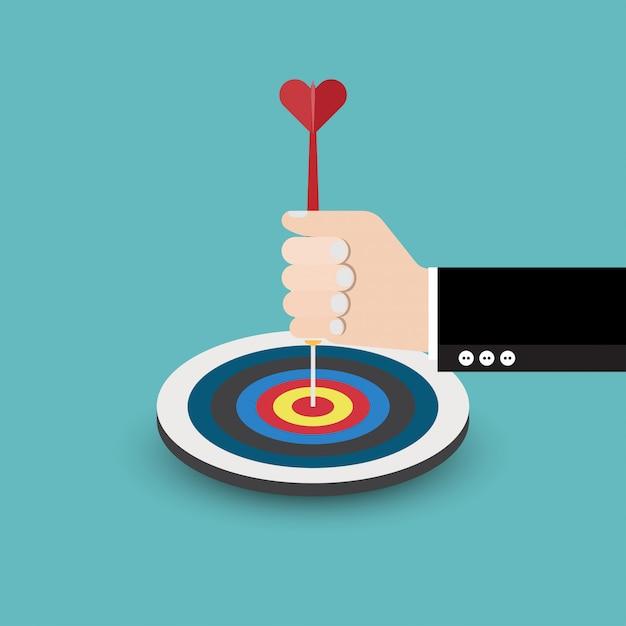 Empresário mão segura uma flecha para o alvo Vetor Premium