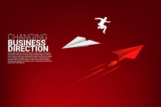 Empresário saltar de avião de papel origami Vetor Premium