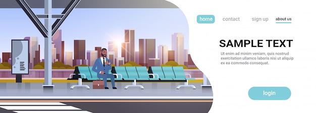Empresário sentado moderno paragem de autocarro homem de negócios com mala esperando transporte público no aeroporto estação paisagem urbana fundo horizontal comprimento total cópia espaço Vetor Premium