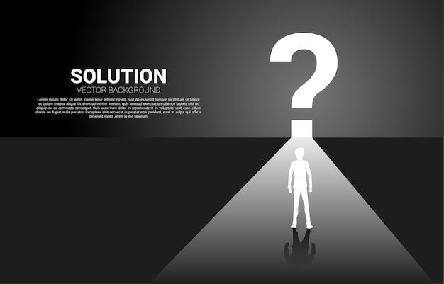 Encontre o conceito de solução. silhueta do empresário correndo para o ícone de ponto de interrogação com iluminação Vetor Premium