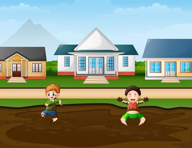 Engraçado crianças jogando uma poça de lama no rural Vetor Premium
