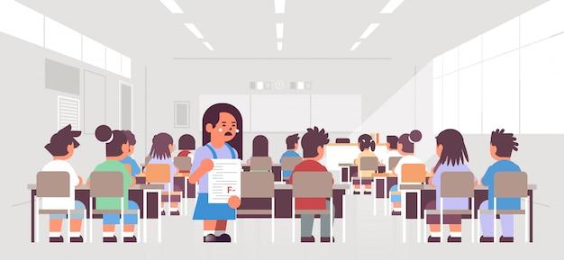 Estudante chorando, segurando, falhou, papel teste, com, mau, grau, vista traseira, alunos, grupo, sentando sala aula, durante, lição, educação, conceito, modernos, classe, sala, interior Vetor Premium