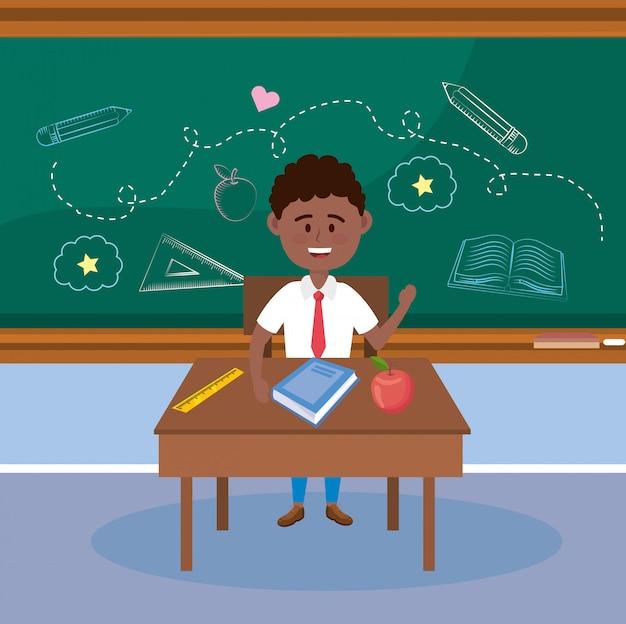 Estudante do menino na mesa com fruta da maçã e livro Vetor grátis