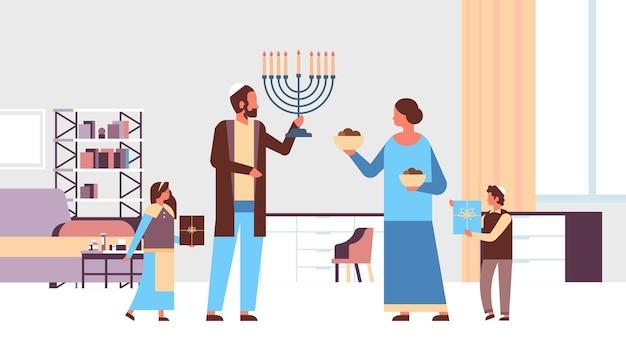 Família de judeus segurando menorá e caixas de presente filhos de pais judeus em roupas tradicionais juntos felizes feriados religiosos do judaísmo hanukkah Vetor Premium
