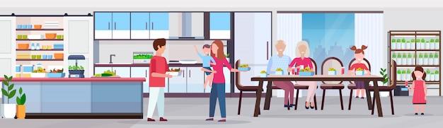 Família de várias gerações tomando café da manhã as pessoas definindo a mesa de jantar cozinha moderna interior plantas inteligentes crescendo sistema conceito horizontal horizontal comprimento total Vetor Premium