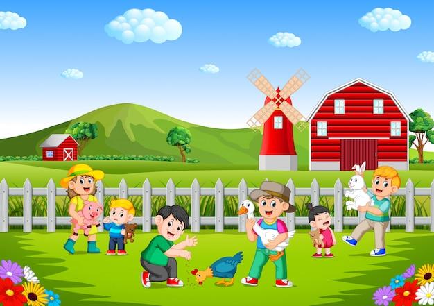 Família e crianças brincando na fazenda se divertindo Vetor Premium