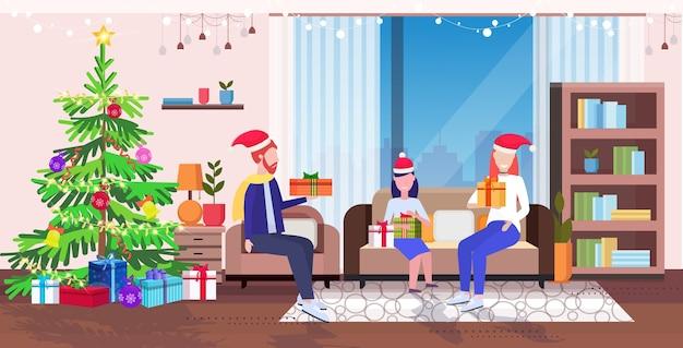 Família feliz no papai noel sentado no sofá perto da árvore do abeto natal ano novo feriados celebração conceito pais e filha segurando caixas de presente na sala de estar Vetor Premium
