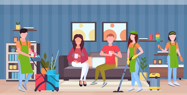 Faxineiros equipe de limpeza em uniforme trabalhando em conjunto com equipamento profissional de limpeza serviço conceito casal sentado no sofá moderna sala interior plana comprimento total horizontal Vetor Premium