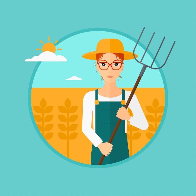 Fazendeiro com o forcado no campo de trigo. Vetor Premium