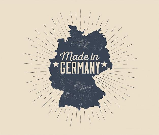 Feito na alemanha distintivo ou rótulo ou etiqueta modelo de design com silhueta negra do mapa da alemanha com sunburst isolado na luz de fundo. ilustração com estilo vintage Vetor Premium