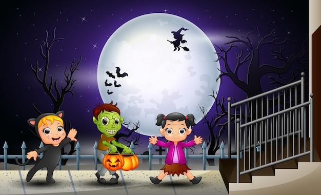 Feliz crianças halloween no fundo de lua cheia Vetor Premium