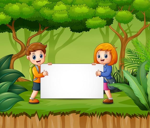Feliz, crianças, segurando, em branco, sinal, em, a, floresta Vetor Premium