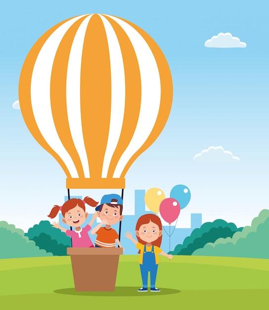 Feliz dia das crianças design com balões de ar quente e crianças felizes dos desenhos animados Vetor Premium