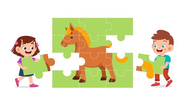 Feliz filhos bonitos jogar resolver quebra-cabeças juntos Vetor Premium