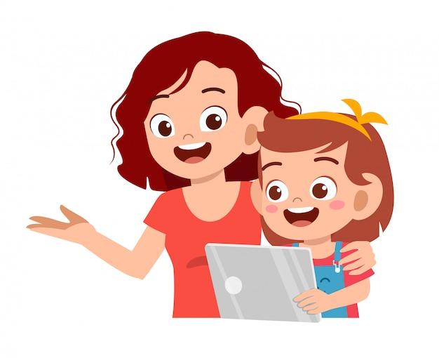 Feliz linda garota jogando tablet com a mãe Vetor Premium