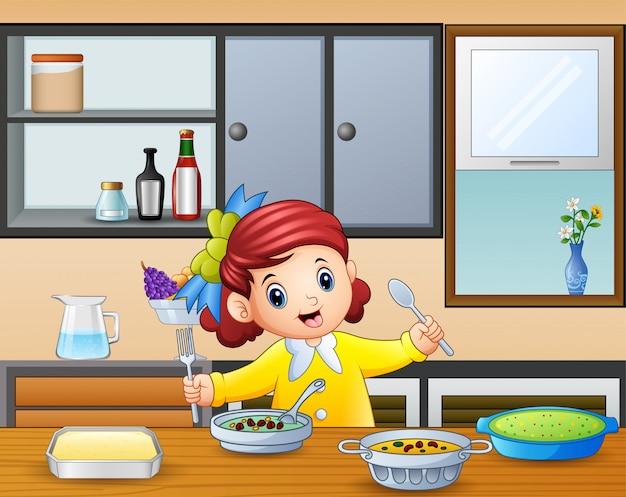 Feliz menina segurando a colher e garfo comendo na mesa Vetor Premium