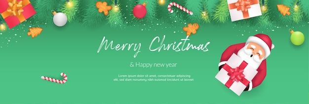 Feliz natal e feliz ano novo. galhos de árvores de natal decorados com doces, caixas de presente e bolinhas. há o papai noel segurando uma caixa de presente e decorada com fundo verde. Vetor Premium