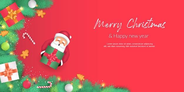 Feliz natal e feliz ano novo. galhos de árvores de natal decorados com doces, caixas de presente e bolinhas. lá está o papai noel segurando uma caixa de presente e decorada com um fundo vermelho. Vetor Premium