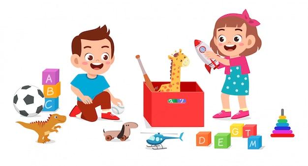 Feliz pequeno garoto garoto e garota brincando com brinquedos Vetor Premium