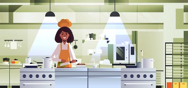 Fêmea profissional chef cozinheiro chopping vegetais placa mulher afro-americano mulher uniforme uniforme salada conceito cozinha restaurante retrato interior cozinha horizontal Vetor Premium