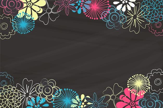 Flores desenhadas à mão sobre fundo de quadro-negro Vetor grátis